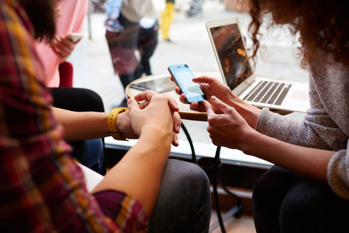 Mulher está fazendo uma compra on-line via telefone celular, enquanto está sentado com os amigos